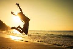 跳跃在海滩的青少年的女孩 免版税图库摄影