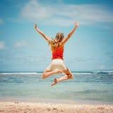 跳跃在海滩的青少年的女孩 免版税库存照片
