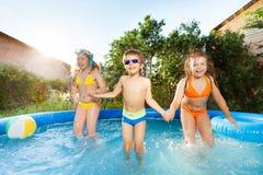 跳跃在游泳池的三个愉快的孩子 库存照片