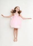 跳跃在演播室的神仙的服装的逗人喜爱的女孩 免版税图库摄影