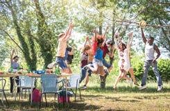 跳跃在烤肉pic nic游园会-与获得年轻愉快的人民的友谊多文化概念的多种族朋友乐趣 免版税库存照片