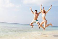 跳跃在热带海滩的天空中的夫妇 图库摄影