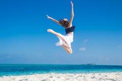 跳跃在热带海滩的女孩 免版税库存图片