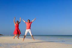 跳跃在热带海滩的愉快的夫妇 库存照片