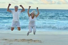 跳跃在热带海滩的年长夫妇 免版税库存图片