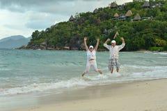 跳跃在热带海滩的年长夫妇 库存图片