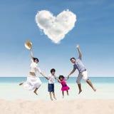 跳跃在爱云彩下的愉快的家庭在海滩 免版税库存照片