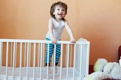 跳跃在白色床上的愉快的小男孩 库存照片