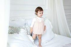 跳跃在白色床上的逗人喜爱的小女孩 免版税库存照片