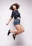 跳跃在白色bac的一名快乐的妇女的全长画象 免版税库存照片