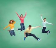跳跃在空气的小组微笑的少年 免版税图库摄影