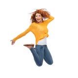 跳跃在空气的微笑的少妇 免版税库存照片