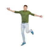 跳跃在空气的微笑的年轻人 库存图片