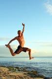跳跃在空气的海滩的运动年轻人 免版税图库摄影