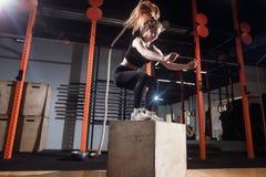 跳跃在箱子训练在健身房,十字架适合的锻炼的健身妇女 免版税库存图片