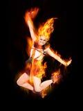 跳跃在红火的少妇 图库摄影