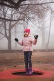 跳跃在绷床的一件桃红色夹克的愉快的女孩户外在公园 秋天,有薄雾的森林 免版税库存图片