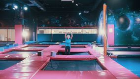 跳跃在绷床的年轻可爱的运动女孩,在体育中心做一些次轻碰 股票录像