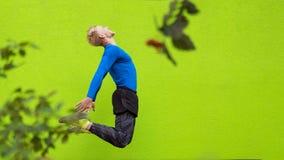 跳跃在绿色背景的年轻坚强男人 库存照片