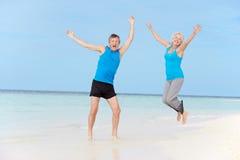 跳跃在美丽的海滩的资深夫妇 库存照片