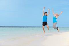 跳跃在美丽的海滩的资深夫妇 免版税库存图片