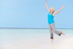 跳跃在美丽的海滩的资深妇女 库存照片