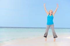 跳跃在美丽的海滩的资深妇女 库存图片