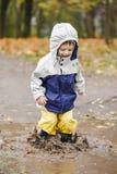 跳跃在胶靴的水坑的愉快的孩子 库存图片