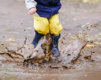 跳跃在胶靴的水坑的愉快的孩子 库存照片