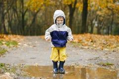 跳跃在胶靴的水坑的愉快的孩子 免版税库存图片