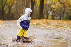 跳跃在胶靴的水坑的愉快的孩子 免版税库存照片