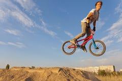 跳跃在自行车的少年 免版税库存图片