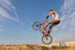 跳跃在自行车的少年 免版税库存照片