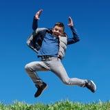 跳跃在草甸的愉快的青少年的男孩 库存照片