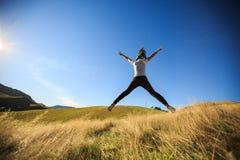 跳跃在草甸的年轻妇女 免版税库存照片