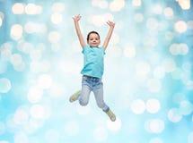 跳跃在蓝色光的空气的愉快的小女孩 免版税库存照片
