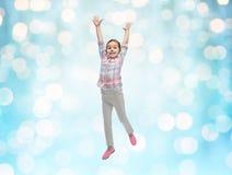 跳跃在蓝色光的空气的愉快的小女孩 库存照片