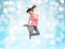 跳跃在蓝色光的空气的愉快的小女孩 免版税库存图片