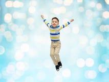 跳跃在蓝色光的空气的愉快的小男孩 免版税库存照片