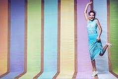 跳跃在蓝色镶边的礼服的愉快的妇女 图库摄影