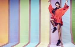 跳跃在起动的流动的橙色礼服的快乐的妇女 图库摄影