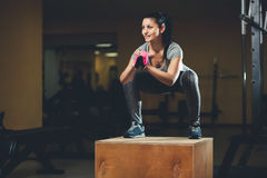 跳跃在镜子前面的一个木箱的亭亭玉立的女孩爱好健美者,当训练在健身房时 图库摄影