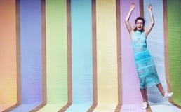 跳跃在镶边蓝色礼服的快乐的妇女 免版税库存照片