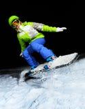 跳跃在雪板的女孩画象在晚上 免版税库存图片