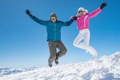 跳跃在雪的夫妇 免版税库存图片