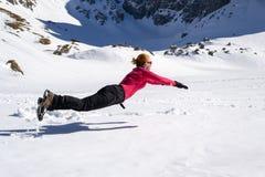 跳跃在雪的快乐的女性徒步旅行者,水平地,类似超人/非凡的女性浮动的姿势,在Malaiesti小屋附 库存图片