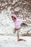 跳跃在雪的愉快的小女孩 免版税库存照片