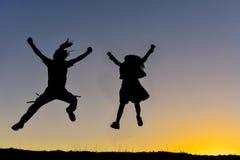 跳跃在领域的夫妇在日落 免版税库存照片