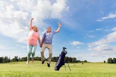 跳跃在高尔夫球场的资深夫妇 免版税库存图片