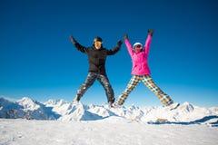 跳跃在高山山的挡雪板愉快的夫妇  免版税库存图片